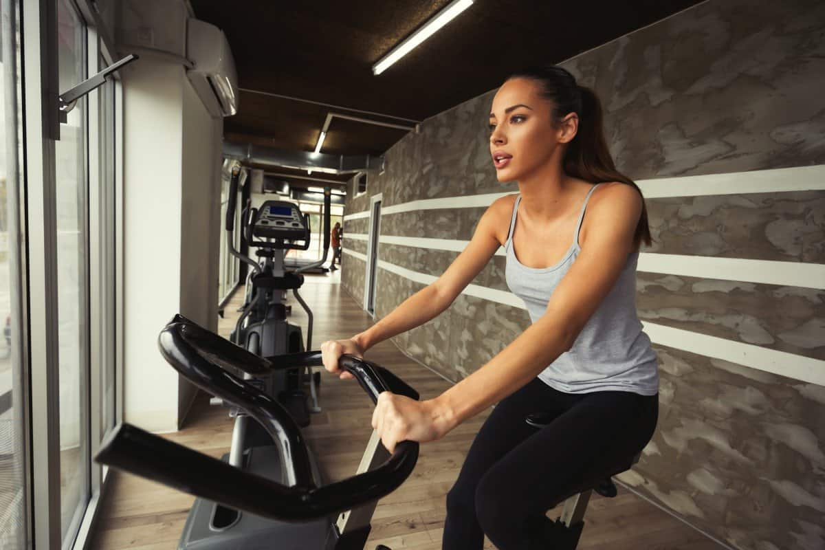 woman doing cardio to slim down on exercise bike