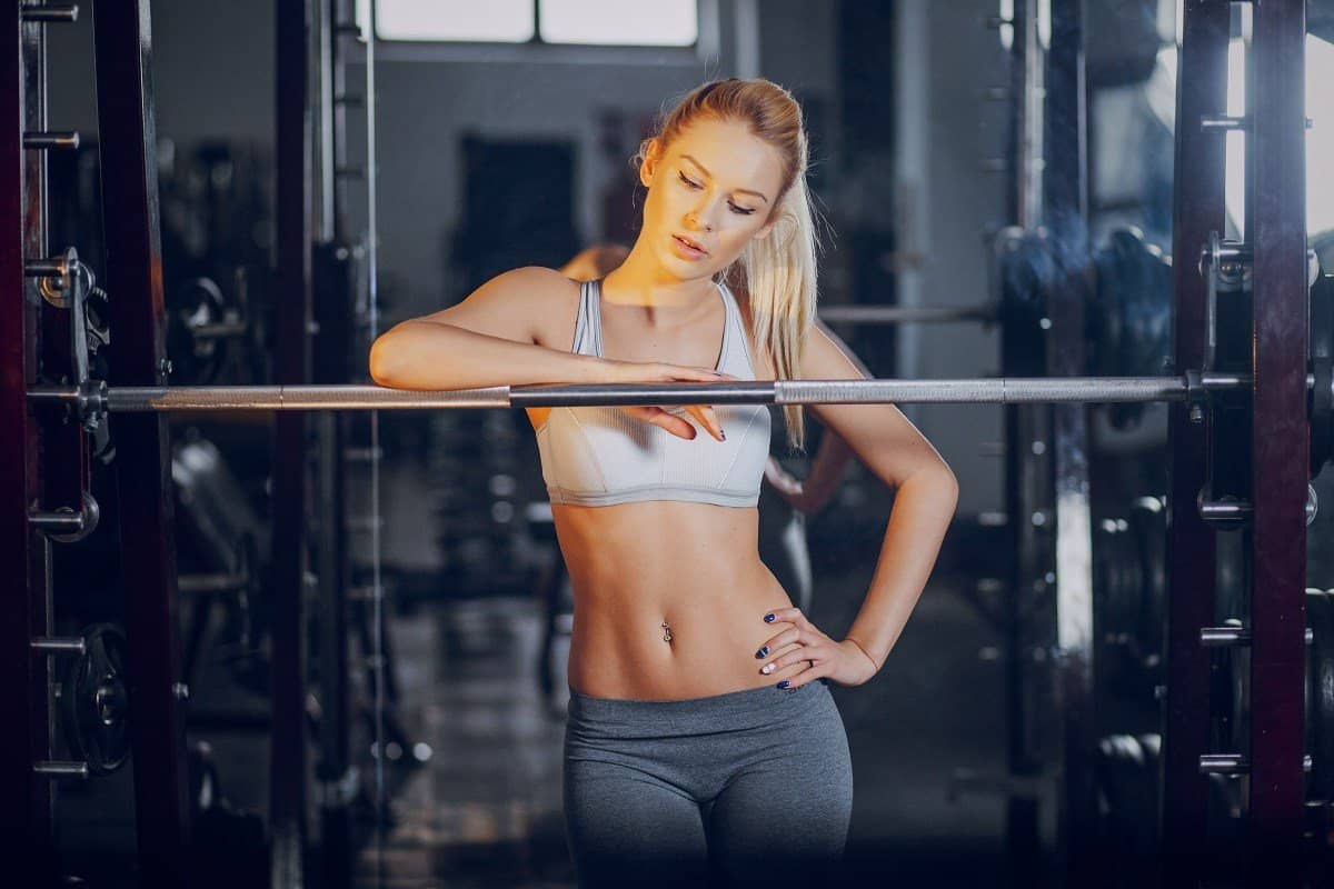 young woman with flat abs leaning on barbell