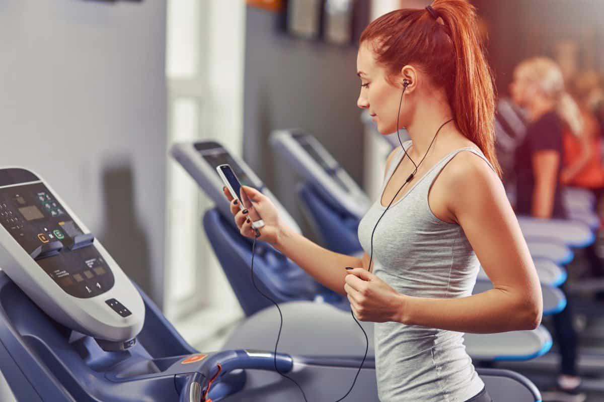 fit woman walking for weight loss on a incline treadmill