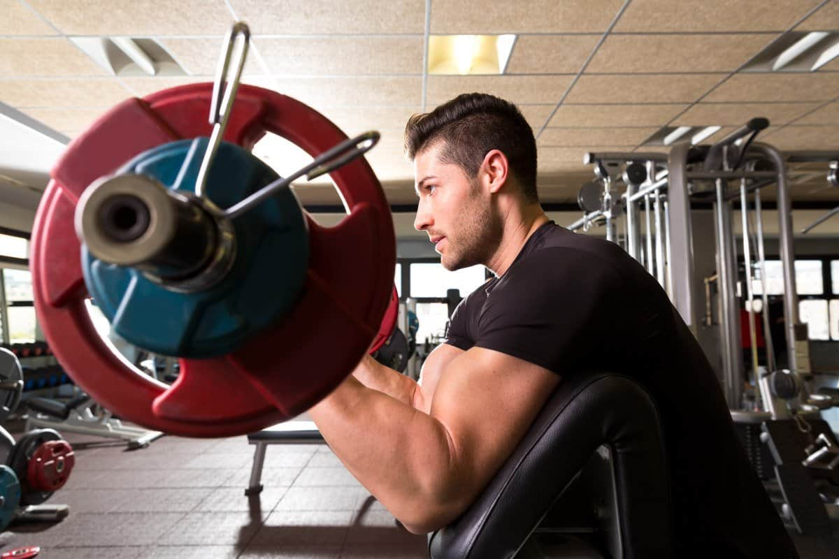 man lifting weights before cardio to lose weight