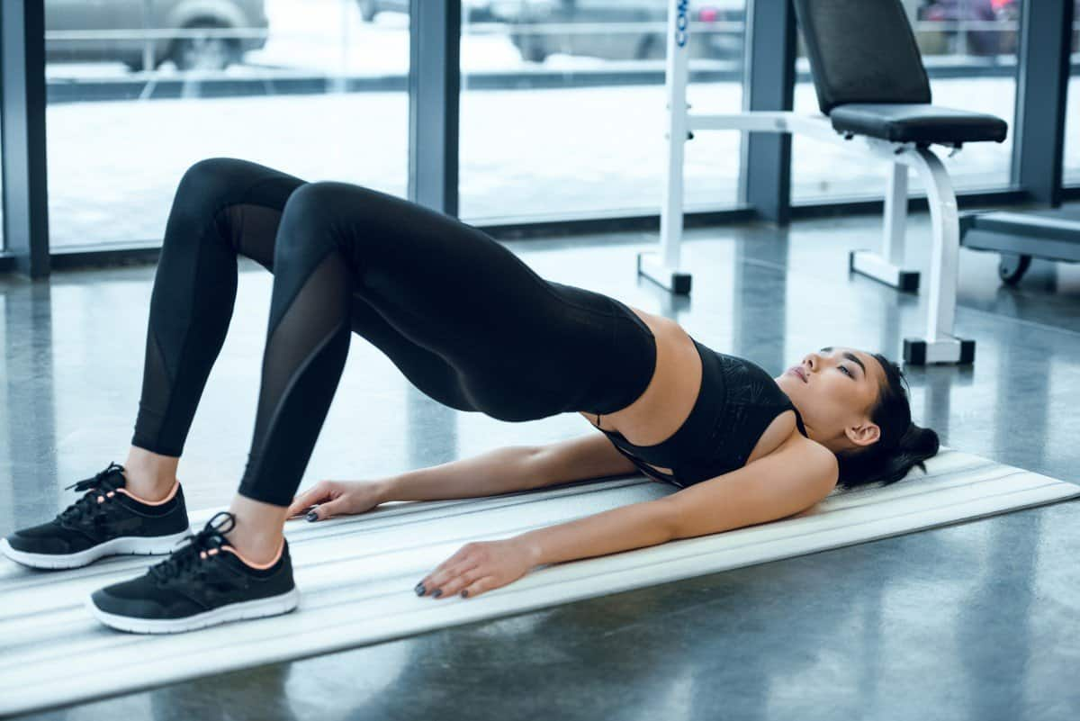 woman doing hip bridge exercise in gym