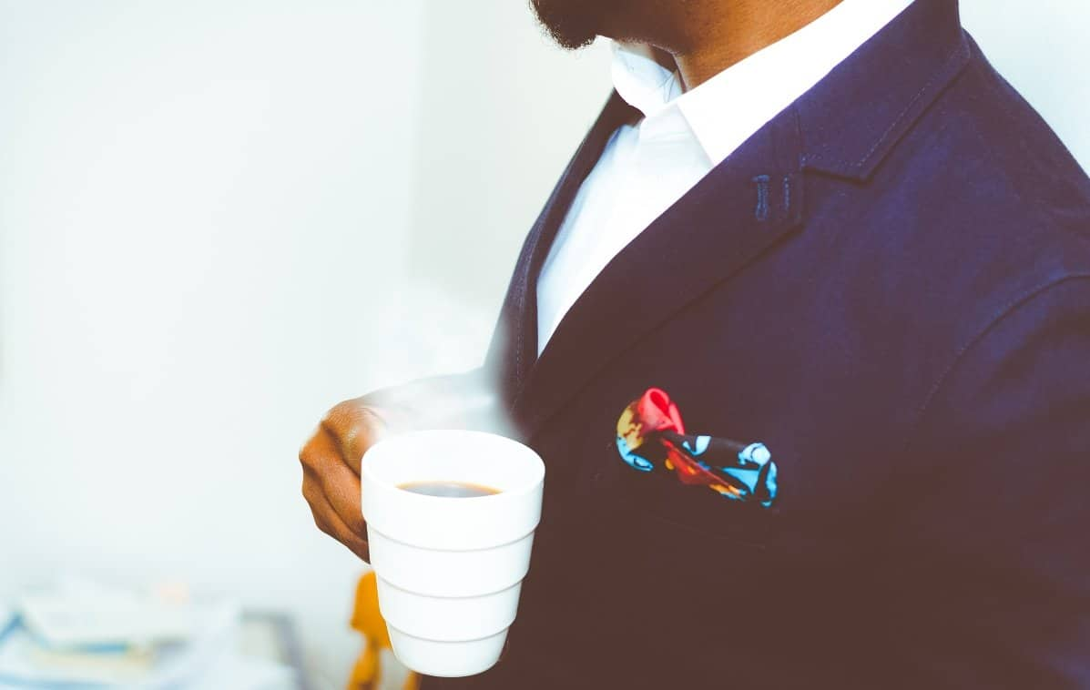 man in suit drinking a white cup of coffee