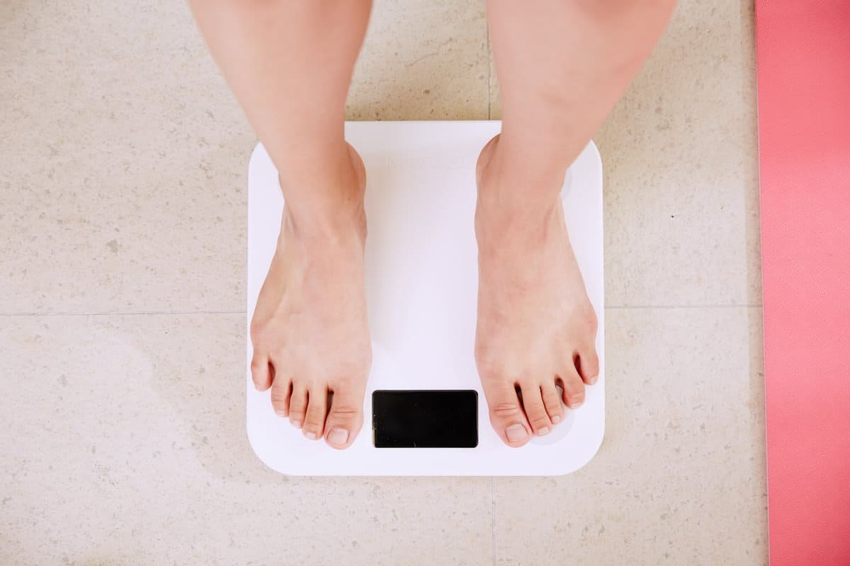woman weighing herself on the scale