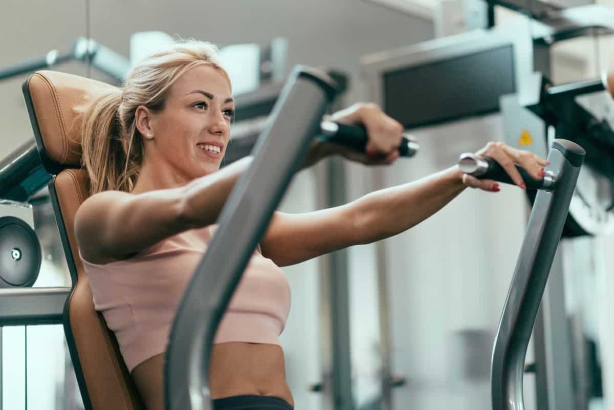 Chest press workout - Beautiful smiling young woman exercising in gym