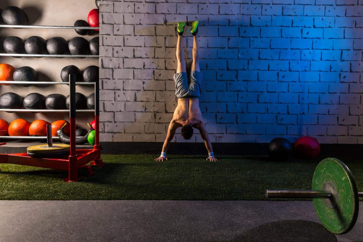 short guy doing handstand push-up against wall