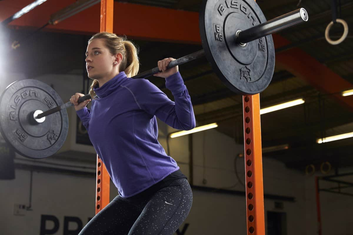 young woman barbell squat